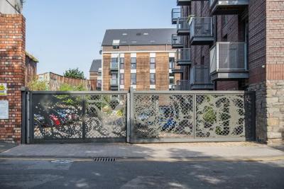 Intricate bespoke design cut into sheet steel for contemporary residential development car park.