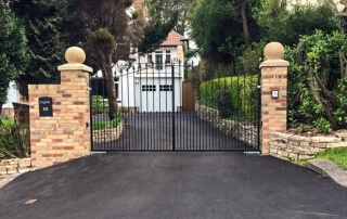 automated steel swinging bell top metal driveway gates with finials and dog bars bristol