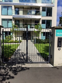 automated steel swinging arch top metal gates in front of private apartment complex