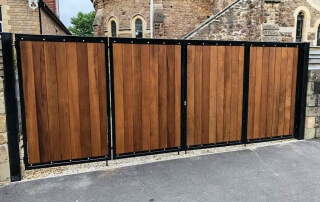 bi-fold flat top domestic automated wood fill metal framed gate in front of historic building